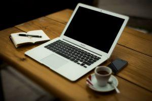 Das Bild zeigt das Handwerkszeug für Journalisten: Laptop, Stift, Notizblock und eine Tasse Kaffee